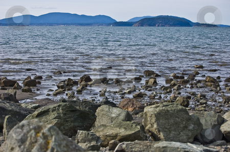 Seascape View of Padilla Bay Washington stock photo, This photo is a seascape shot of the view at Padilla Bay Washington overlooking Hat Island off to the distance.  Beautiful ocean scene with rocks in the foreground and lots of muted blues. by Valerie Garner