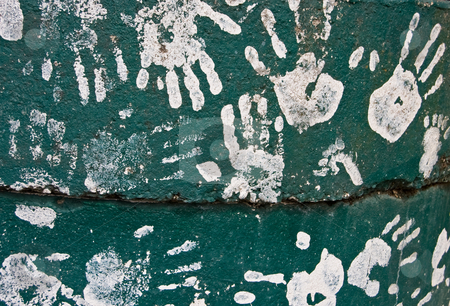 Kids Handprints on Green Painted Cement stock photo, This is a collection of kid's handprints in white paint, set against a green cement background. by Valerie Garner
