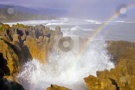 Making Miracles stock photo, An eruption of spray from Punakaiki (The Pancake Rocks) creates a rainbow over the jagged limestone fins carved by the pounding of the Tasman Sea by Mike Dawson