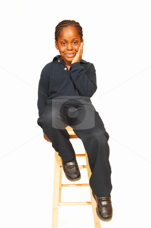 Young Jamaican boy. stock photo, A friendly young Jamaican boy in the studio sitting on an bar chair and  wondering what is going on around him. by Horst Petzold