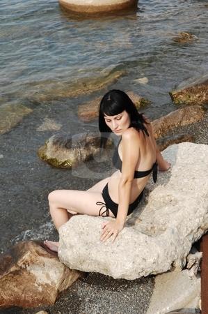 Bikini model on the beach. stock photo, Young beautiful bikini girl sitting on a big rocks on the beach of  lake Ontario. by Horst Petzold