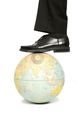 Businessman steps on globe stock photo, Businessman rests his foot on a globe by Rick Becker-Leckrone