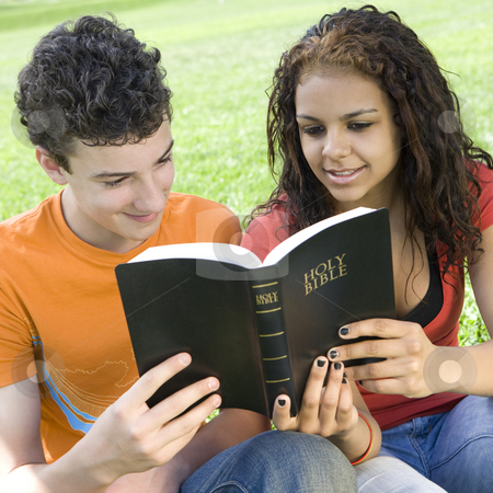 Two teens share bible stock photo, Two teens share a bible in a park by Rick Becker-Leckrone