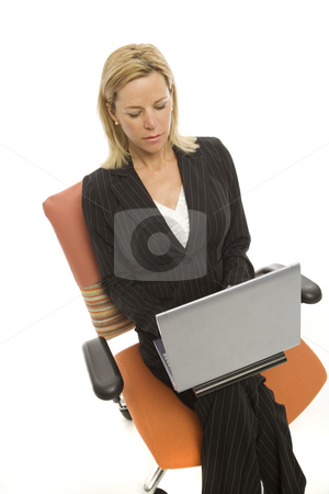 Businesswoman sits with laptop stock photo, Businesswoman in a suit sits with a laptop in a chair by Rick Becker-Leckrone