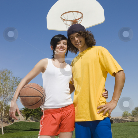 Teen basketball couple stock photo, Teen basketball couple hangs out at a court by Rick Becker-Leckrone