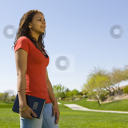 Teen with bible in park stock photo, A happy teen girl holds a bible in a park by Rick Becker-Leckrone