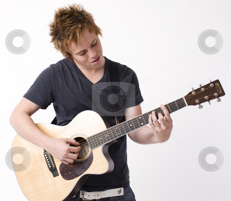 Boy plays guitar stock photo, A boy plays acoustic guitar by Rick Becker-Leckrone