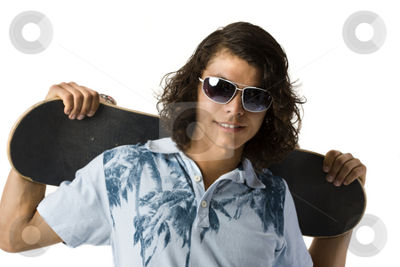Boy with skateboard stock photo, A boy holds a skateboard behind his back by Rick Becker-Leckrone