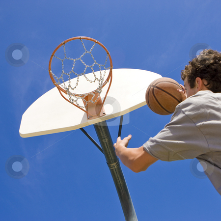 Basketball player jumps for hoop stock photo, A teen basketball player jumps to shoot at the basket by Rick Becker-Leckrone