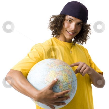 Boy points to globe stock photo, A teen boy holds a globe, smiles, and points to it by Rick Becker-Leckrone