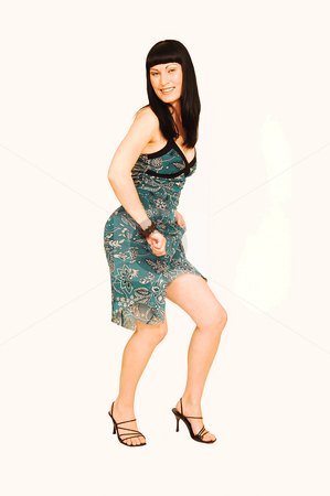 Standing woman in green dress. stock photo, A young pretty woman standing in an studio wearing a green dress with black ornaments printed on by Horst Petzold
