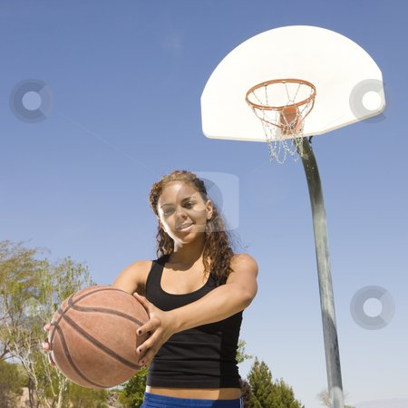 Teen with basketball at a court stock photo, A teen with a basketball hangs out at the court by Rick Becker-Leckrone