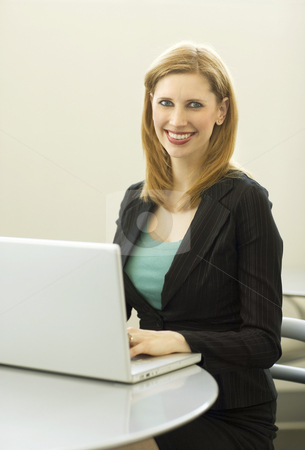 Businesswoman uses laptop stock photo, Businesswoman smiles as she uses a laptop by Rick Becker-Leckrone