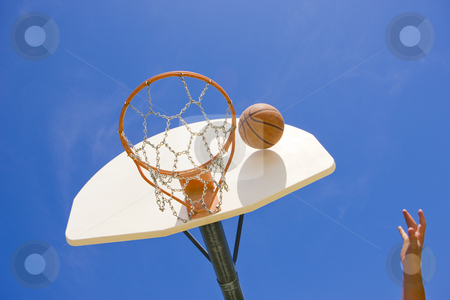 Basketball reaches hoop stock photo, A basketball player throws a basket by Rick Becker-Leckrone