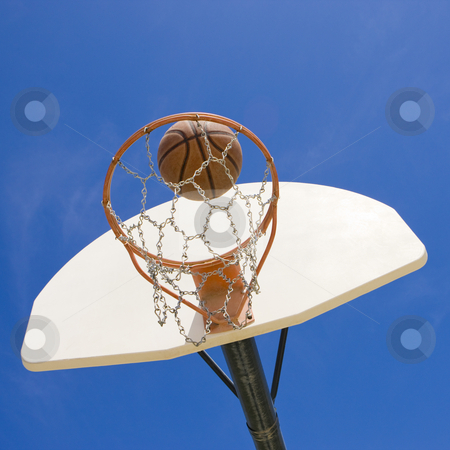 Basketball hoop and ball stock photo, A basketball goes through a basketball hoop by Rick Becker-Leckrone