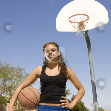 Teen girl with basketball stock photo, A teen girl with a basketball hangs out at park by Rick Becker-Leckrone