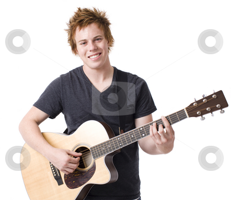 Boy with guitar stock photo, A boy smiles as he plays a guitar by Rick Becker-Leckrone
