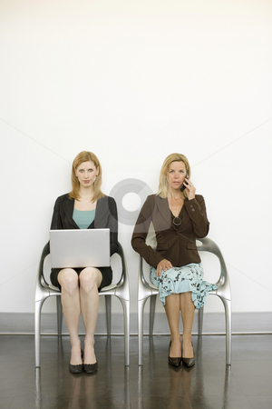 Workers sit in chairs stock photo, Two women sit in metal chairs and work by Rick Becker-Leckrone