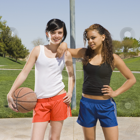 Two teens play basketball stock photo, Two teen girls hang out at a basketball court by Rick Becker-Leckrone