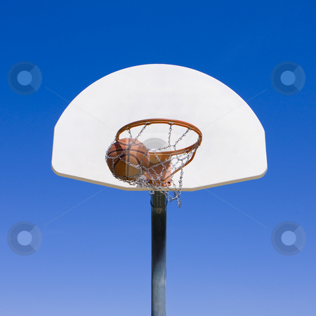 Basketball goes through hoop stock photo, A basketball goes through hoop by Rick Becker-Leckrone