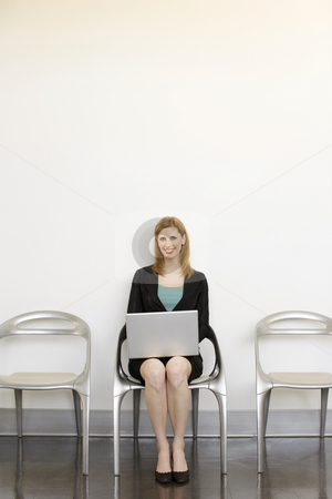 Businesswoman sits using laptop stock photo, Businesswoman sits in a chair using a laptop by Rick Becker-Leckrone