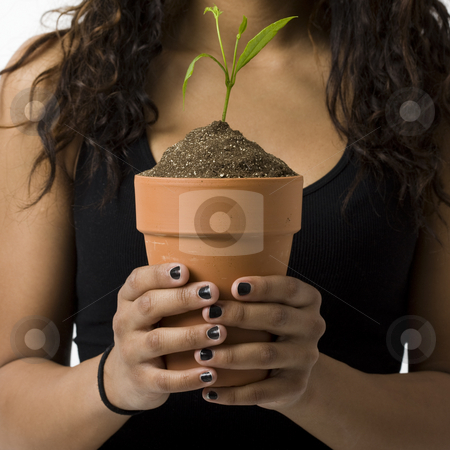 Girl with potted plant stock photo, A girl holds a potted plant by Rick Becker-Leckrone