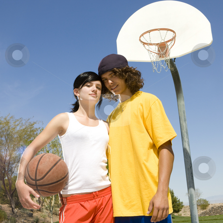 Teen basketball couple stock photo, Teen basketball couple hangs out at a park's court by Rick Becker-Leckrone