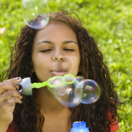 Girl blows bubbles stock photo, A teenage girl blows bubbles with a wand by Rick Becker-Leckrone