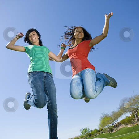 Happy teens jump in air stock photo, Happy teens jump in air by Rick Becker-Leckrone