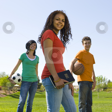 Three teens with bible stock photo, Three teens with bible hang out at a park by Rick Becker-Leckrone