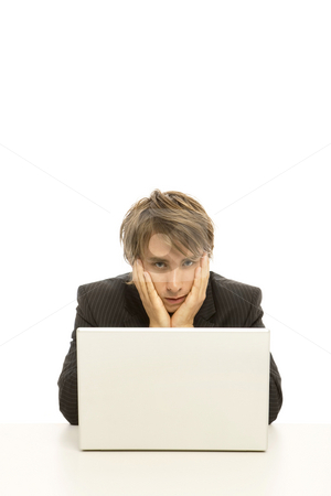 Businessman uses laptop stock photo, Businessman holds his head in his hands as he look at a laptop by Rick Becker-Leckrone
