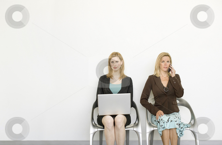 Busineswomen sit in chairs and work stock photo, Two businesswomen sit in chairs and work by Rick Becker-Leckrone