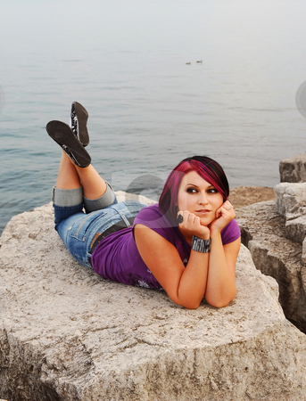 Girl lying on lakeshore. stock photo, An red hair girl in jeans lying on the shore of lake Ontario at sunset. by Horst Petzold