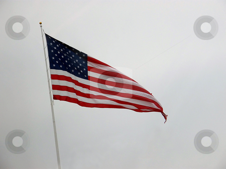 High Flying American Flag stock photo, American Flag Flying High in the breeze on an overcast winter day. by Dazz DeLaMorte