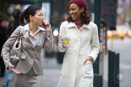 City Business Women stock photo, Two business women walking in the big city. One is on her cell phone. by Todd Arena