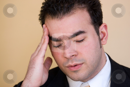 Man With a Headache stock photo, Young man with a headache. He might be experiencing intense stress over a time of economic downturn or other financial hardship. by Todd Arena