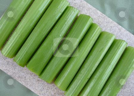 Freshly cut green celery stalks stock photo, Fresh sliced and chopped celery on cutting board by Jill Reid