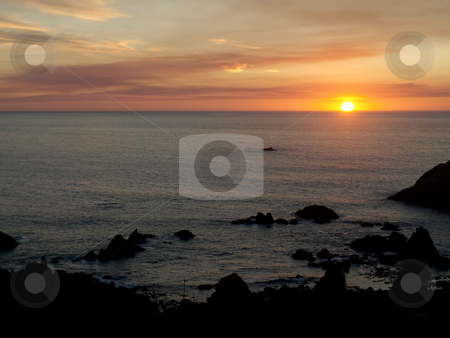 Ball of fire on the horizon stock photo, The sun appears as a blazing ball of fire as it sets on the ocean horizon by Jill Reid