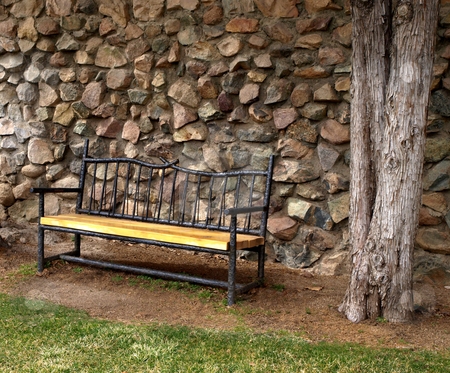 Iron and wood bench against stone wall stock photo, Wrought iron and wooden bench against a stone wall by Jill Reid