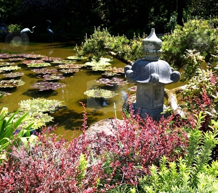 Statue and lily pads in pond stock photo, Colorful view of foliage, lily pads and statue in pond by Jill Reid