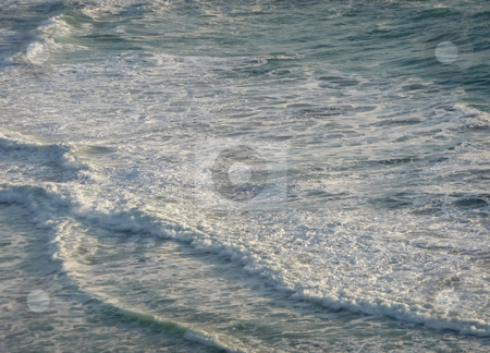 Foaming gentle waves along the coast 250A stock photo, Foamy gentle waves roll into shore, lit by the sun by Jill Reid
