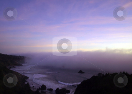 Foggy wave covers the beach stock photo, A wave of fog rolls in over an Oregon coastline by Jill Reid