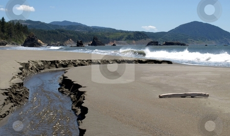 Riptide on the beach along the Oregon coastline stock photo, Rock outcroppings and a gentle surf on the beach in Oregon by Jill Reid