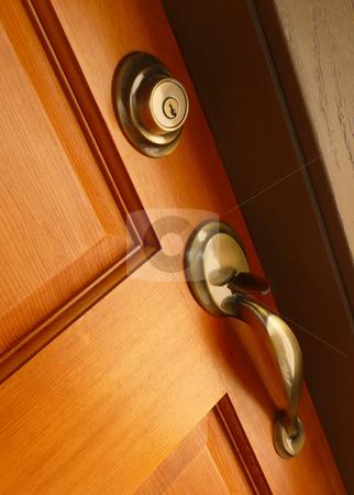 Contemporary door handle and deadbolt stock photo, Brass door handle and deadbolt on wooden door by Jill Reid