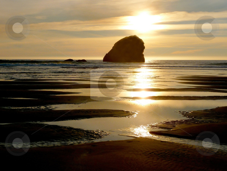 Coastal Sunset with rock formation stock photo, An evening sunset on the coast with reflective pools of water and sand and outlying rock formation by Jill Reid