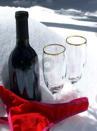 Wine, glases and red bikini in snow stock photo, Enticing setting ofwine, crystal glasses and red bathing suit in the snow by Jill Reid