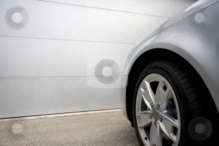 Garage door stock photo, A silver car sits in front of a garage by Angus Benham