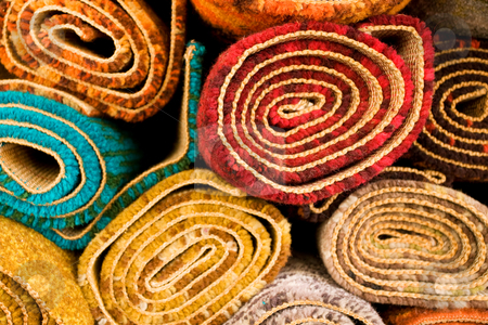 Colored Rugs stock photo, Section detail of a pile of colorful rugs by Angus Benham