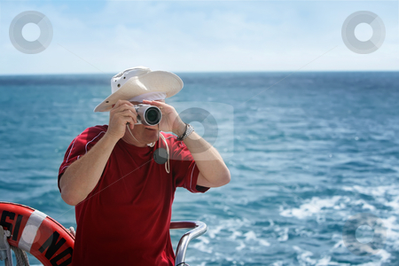 Photography enthusiast stock photo, A middle aged man takes photos from a boat by Angus Benham