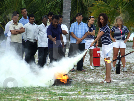 Putting out the fire stock photo, A group of people attending a training course on putting out fires for hotel management on a tropical Maldivian Island for a popular resort chain. by Chris Alleaume